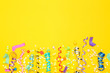 Leinwanddruck Bild - Colorful ribbons with paper stars and confetti on yellow background