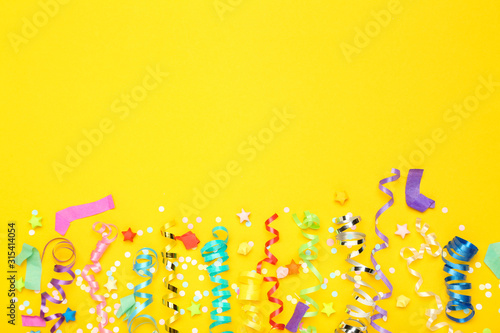 Obraz Colorful ribbons with paper stars and confetti on yellow background - fototapety do salonu