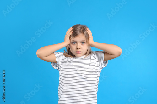Worried little girl on light blue background