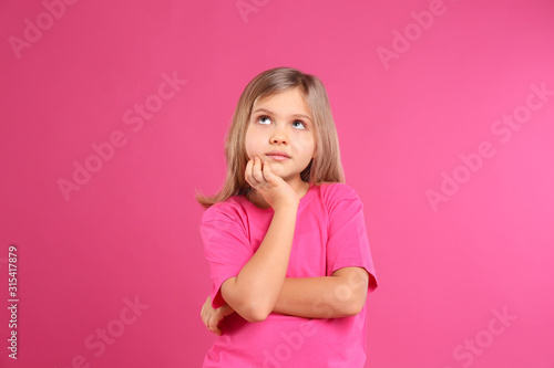 Obraz Thoughtful little girl wearing casual outfit on pink background - fototapety do salonu