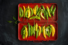 Overhead View Of Yellow And Green Chillies (Capsicum) With Leaves And Flowers In Red Box