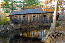 Old New England Covered Bridge Over Calm River. Reflection Of Bridge In Water During Autumn Season
