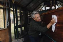 Senior Man Cleaning Wooden Boa...
