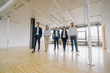 Portrait of confident business people walking in office