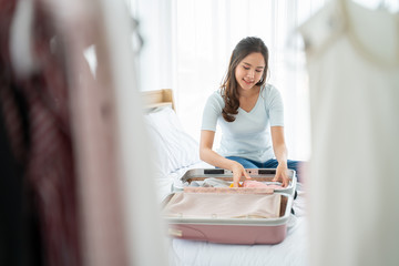 Traveler,people,Tourism and holiday concept.Happy woman ready for travel with suitcase.Female hands packing traveler case on bed at home or hotel room.
