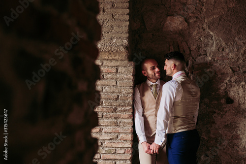 Affectionate elegant gay couple in an old building - 315423647