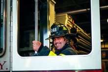 Portrait Of Happy Firefighter Getting Into Fire Engine, New York, United States