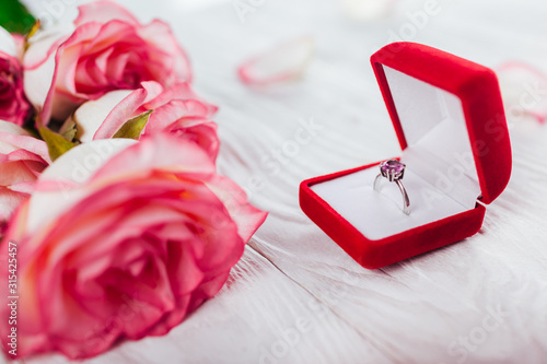 Fotografia, Obraz Silver ring with amethyst gem in red gift box and bouquet of roses