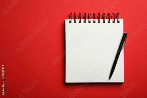 Fototapeta Stylish open notebook and pen on red background, top view. Space for text obraz