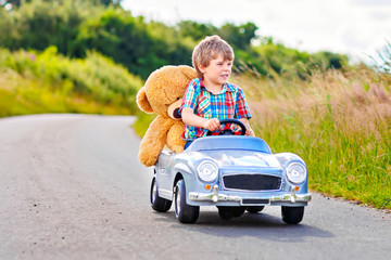 Little preschool kid boy driving big toy car and having fun with playing with...
