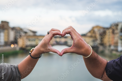 Photo Young couple hands united in a heart shape. Florence Italy