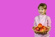 canvas print picture - child 7-8 years old holds a basket with fresh fruits