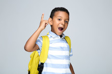 Young African American School Boy With Backpack On Grey Background