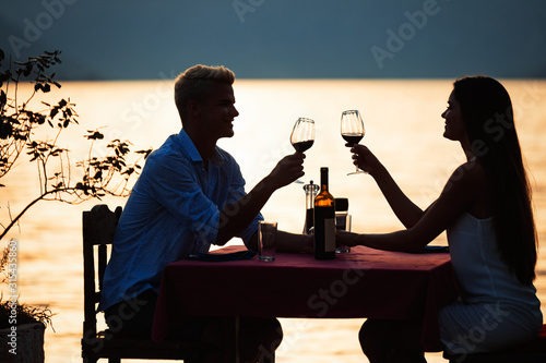 Fotografía Happy couple on summer evening having romantic dinner outdoor
