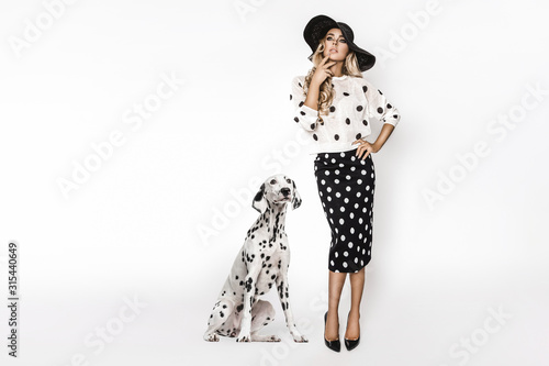 Photo Attractive stylish blonde model in black and white clothes stand near  dalmatian dog