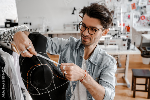 Attractive professional serious stylish tailor with glasses in a blue shirt working next to a wooden table with threads, an apron and scissors in an amazing modern studio and mannequin Fototapeta