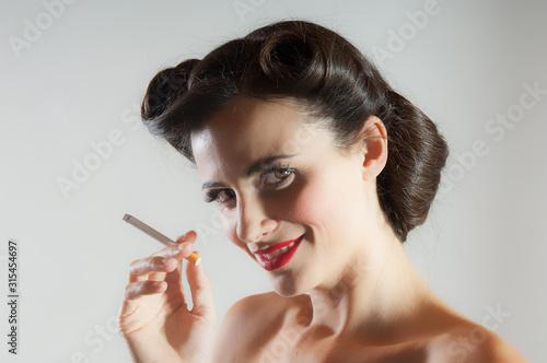 Obraz Donna di profilo tiene la sigaretta in mano - fototapety do salonu