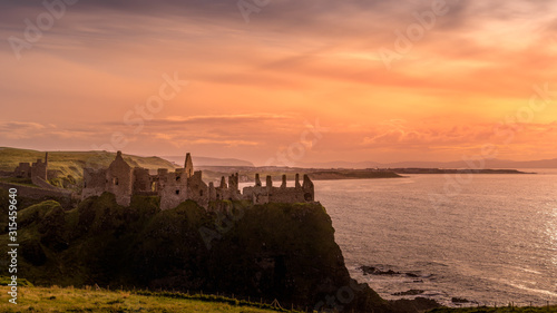 Photo Ruined medieval Dunluce Castle on the cliff at amazing sunset, Wild Atlantic Way, Bushmills, County Antrim, Northern Ireland