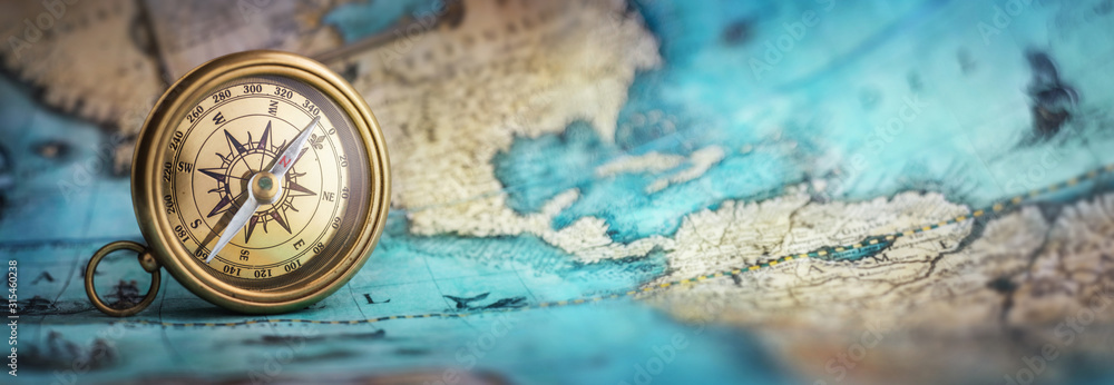 Fototapeta Magnetic old compass on world map.Travel, geography, navigation, tourism and exploration concept background. Macro photo. Very shallow focus.