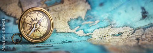 Magnetic old compass on world map.Travel, geography, navigation, tourism and exploration concept background. Macro photo. Very shallow focus. #315460238