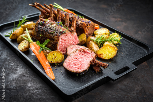 Barbecue rack of lamb with carrot and potatoes offered as closeup on a modern de Fototapet