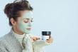 Leinwanddruck Bild - modern woman with green facial mask holding cosmetic jar
