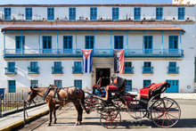 Tourist Carriage With Horses On The Street In The Old Center Of Havana And A Large Cuban Flag On The Facade Of The Old House