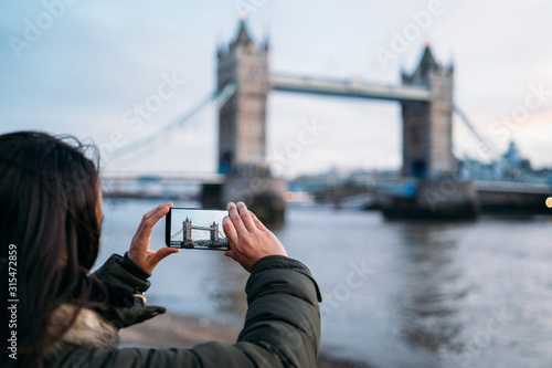 Valokuvatapetti Woman taking a photo with the smart phone to the Tower Bridge in London on a sunny winter day, London, Great Britain
