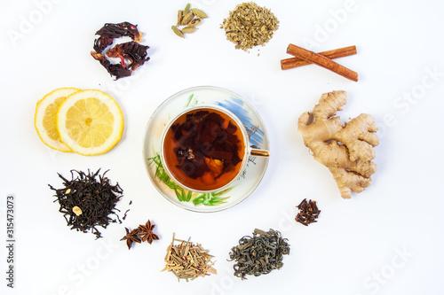 Fototapeta  Filiżanka z herbatą otoczona różnymi gatunkami herbat oraz rozgrzewającymi leczniczymi przyprawami i dodatkami do herbaty obraz