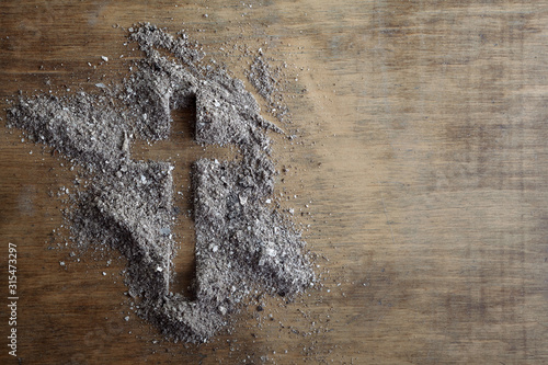 Christian cross symbol made of ash on a wooden background Fototapete
