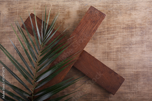 Palm Sunday. Palm brunch on wooden background with cross. Easter Fototapete