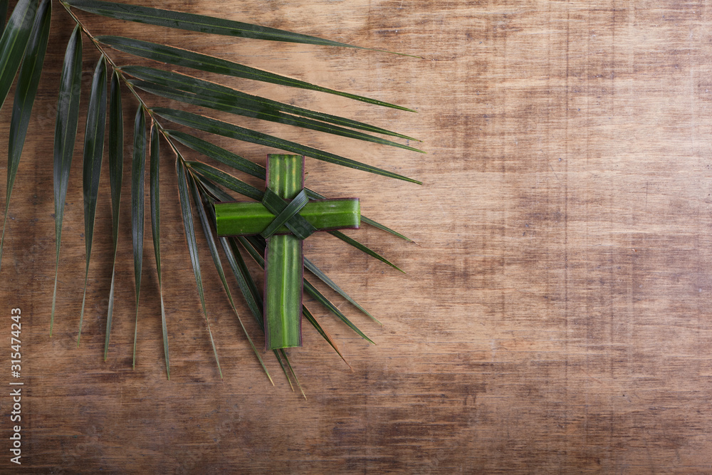 Fototapeta Palm sunday concept: Cross shape of palm branch on an antique wooden background