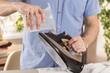 Męska dłoń trzyma pojemnik i nalewa wodę do żelazka. Prasowanie, obowiązki domowe wykonywane przez mężczyzn.
