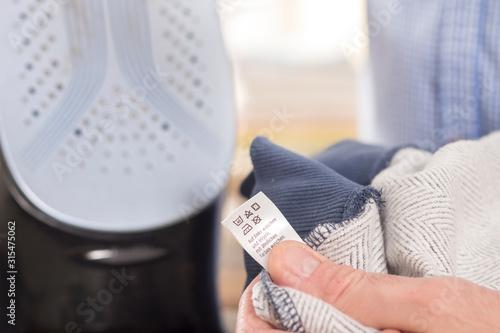 Fototapeta Męska dłoń trzyma ubranie z metką na której widnieją piktogramy jak prać i prasować odzież. Srebrna podstawa żelazka stoi na drugim planie. obraz