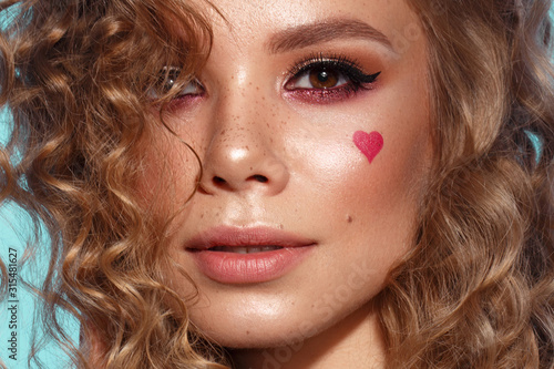 Pretty girl with curls hairstyle, classic makeup, freckles, nude lips and manicure design with hearts Wallpaper Mural