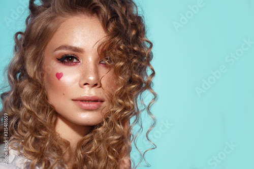 Obraz Pretty girl with curls hairstyle, classic makeup, freckles, nude lips and manicure design with hearts. Beauty face. The image for Valentine's Day - fototapety do salonu