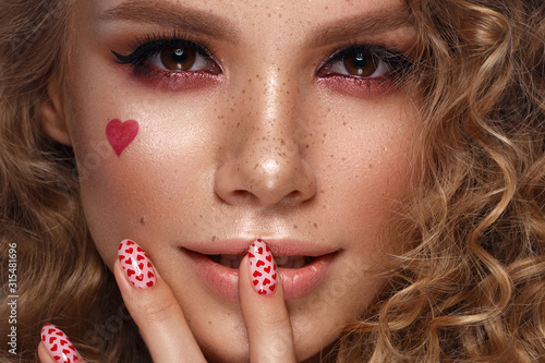 Pretty girl with curls hairstyle, classic makeup, freckles, nude lips and manicure design with hearts. Beauty face. The image for Valentine's Day