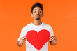 canvas print picture - Be my valentine. Romantic cute african-american guy searching for true love, folding lips and give kiss camera, holding large cute heart cardboard, standing orange background show affection