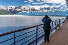 Woman Is Wearing A Stripes And Taking A Picture Of Hubbard Glacier On Her Mobile Phone. Lady Is Crew Member On A Cruise Ship. Working As A Ships Officer. Snowy Mountains And Iceberg.