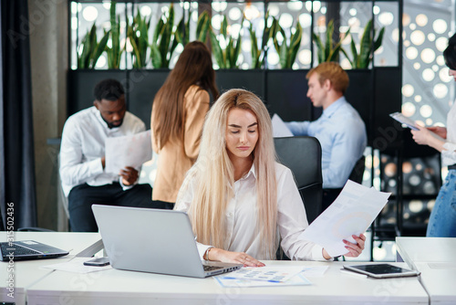 Fototapeta  Pretty purposeful young female office manager entering datas from financial repo