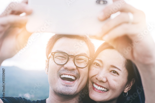 couple love concept.asian lover man and women taking a selfie while travelling on holiday hug each other.photo of people smile enjoy  Beautiful romantic time - 315530467