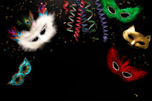 Carnival Objects On A Black Background. Coiled Streamers, Masks, Confetti