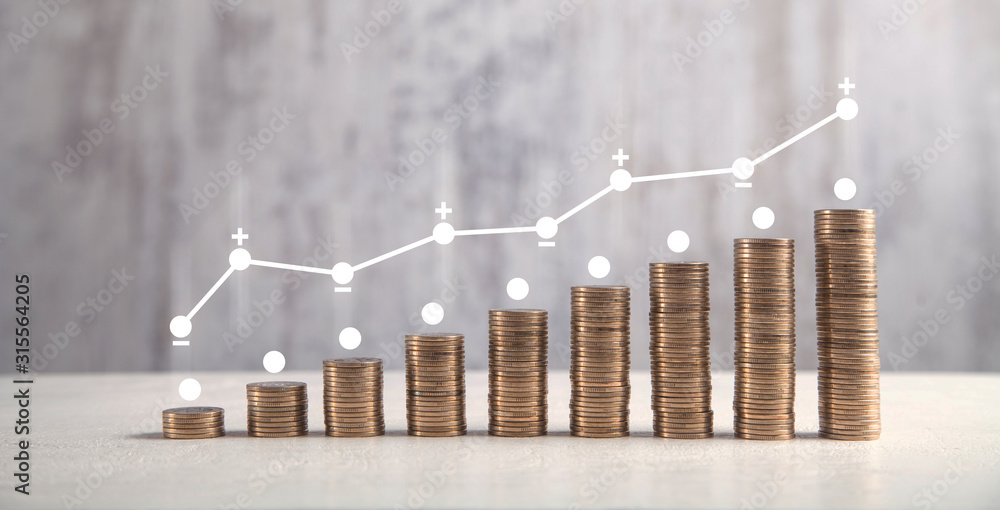 Fototapeta  Coins on white table with profit graph.