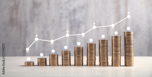 Coins on white table with profit graph.
