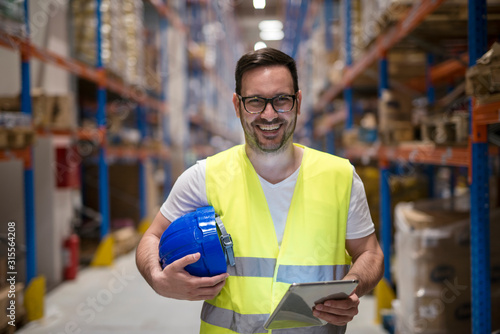 Fototapeta Portrait of smiling caucasian warehouse worker with tablet standing in storage department. obraz
