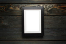 Black Frame Hanging On The Dark Wooden Wall