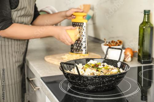 Cuadros en Lienzo Woman cooking delicious risotto, closeup. Tasty recipe