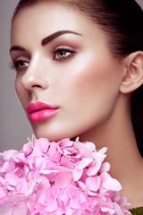 Panel Szklany Do salonu kosmetycznego Portrait of beautiful young woman with flowers. Brunette woman with luxury makeup. Perfect skin. Eyelashes. Cosmetic eyeshadow