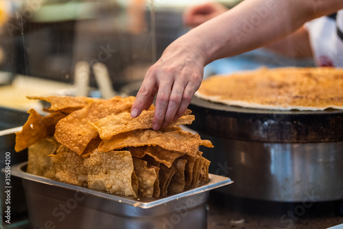 Fotografía  Closeup of person cooking crepe crespelle traditional dessert in Florence, Italy