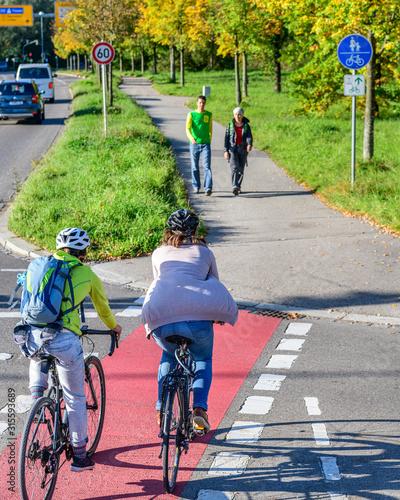 Fotografía Radfahrer fahren vom Radweg auf einen kombinierten Rad- und Gehweg mit Fußgänger